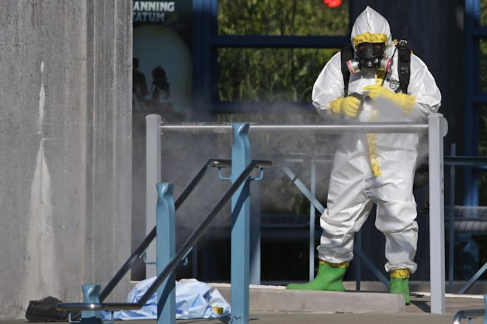 A first responder wears a full biohazard suit while spraying a disinfecting solution on the railing at the Dallas Area Rapid Transit (DART) White Rock Station after a woman with Ebola-like symptoms fell ill at the station October 18, 2014 in Dallas, Texas.