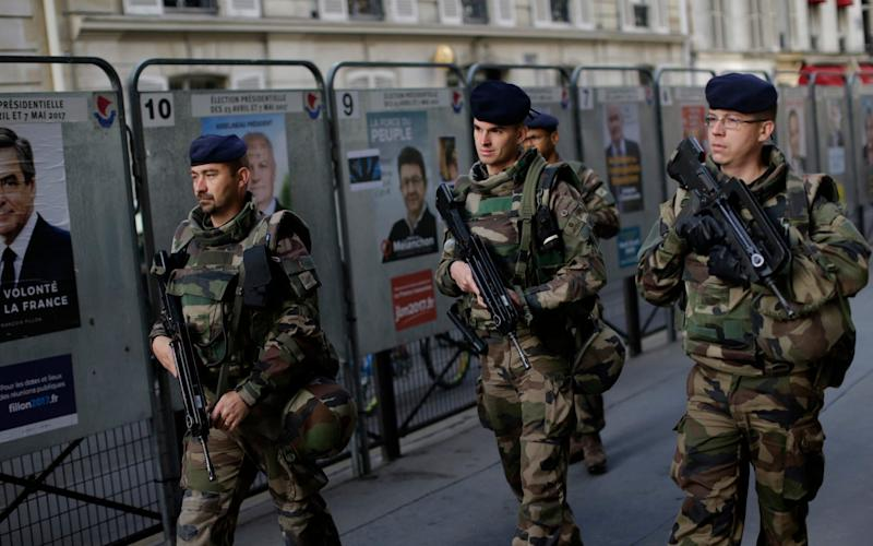 Army soldiers patrol past posters showing faces of the candidates for the first-round presidential election near a polling station in Paris - Credit: Emilio Morenatti/AP