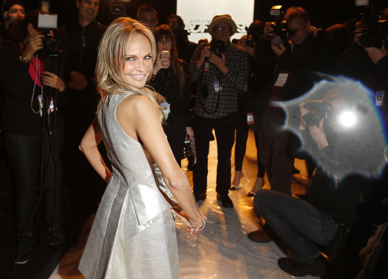 Actress Kristin Chenoweth poses for photographers as she stands on the runway before the Project Runway show at Fashion Week February 8, 2013.  REUTERS/Carlo Allegri  (UNITED STATES - Tags: FASHION SOCIETY ENTERTAINMENT) - RTR3DIB0