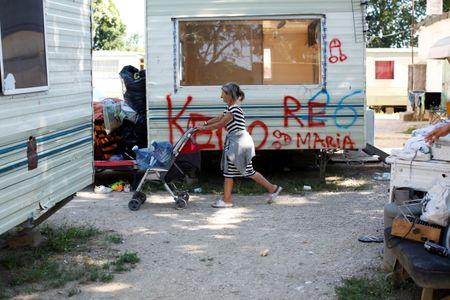 A woman walks past pre-fabricated homes seized by Police in an official Roma camp in Rome, Italy June 27, 2018. Picture taken June 27, 2018.  REUTERS/Tony Gentile