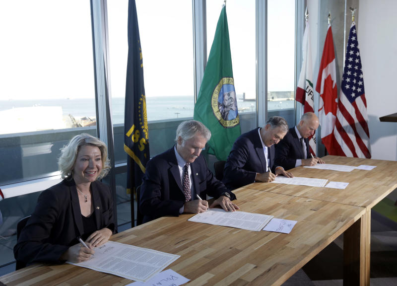 From left, Mary Polak, environment minister of British Columbia, representing British Columbia premier Christy Clark, Oregon Gov. John Kitzhaber, Washington Gov. Jay Inslee and California Gov. Jerry Brown sign an agreement to collectively combat climate change on Monday, Oct. 28, 2013, in San Francisco. The group will work together to coordinate efforts with the hope of stimulating a clean-energy economy in a region with a combined gross domestic product of $2.8 trillion. (AP Photo/Marcio Jose Sanchez)