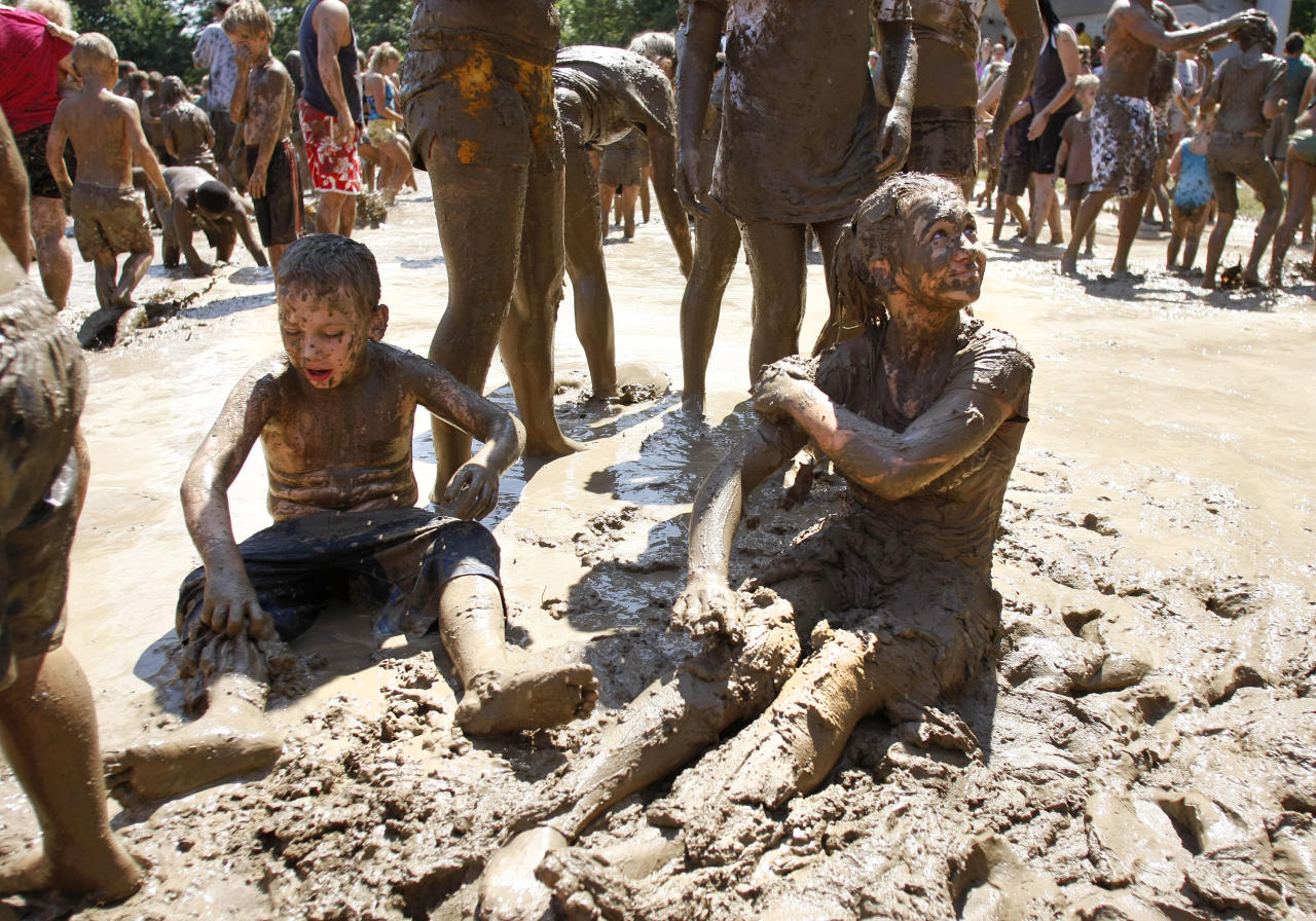 """Kids play in a giant lake of mud at the 25th annual """"Mud Day"""" July 10, 2012 in Westland, Michigan. The event, which features a 75' by 150' pit filled with 20,000 gallons of water and 200 tons of topsoil, draws about a thousand children each year. (photo by Bill Pugliano/Getty Images)"""