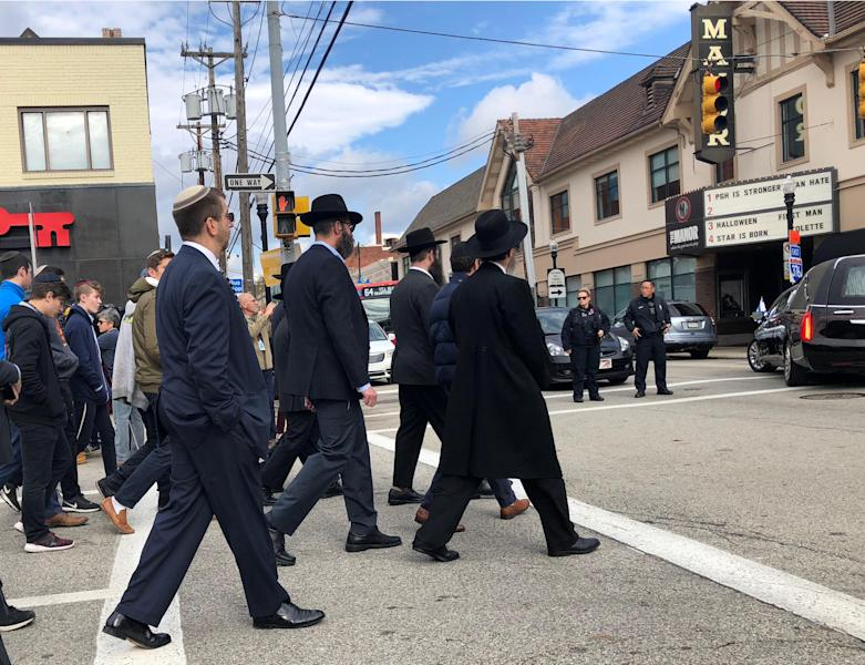 """Mourners follow the hearse on foot after the funeral of Tree of Life Synagogue shooting victim Jerry Rabinowitz in Pittsburgh, Pennsylvania, U.S. October 30, 2018. The sign on the movie theater at right reads """"PGH is stronger than hate"""". REUTERS/Jessica Resnick-Ault"""