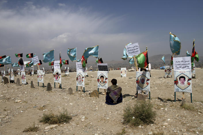 An Afghan young boy site near to the grave of his classmate, adorned with his picture, on the outskirts of Kabul, Afghanistan, Monday, Sept 14, 2020. Scores of friends and families of students who were killed in local conflicts are gathering in a cemetery to call for a permanent countrywide ceasefire from the parties to the intra-Afghan peace conference taking place in Doha, Qatar. (AP Photo/Rahmat Gul)