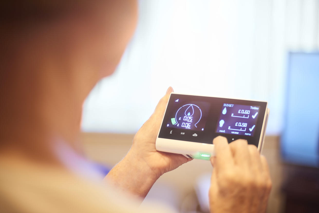 Close up of home owner checking energy consumption on smart meter home technology. They can see their energy consumption and billing all in one place and live costs. Graphics and all identifying have been altered.