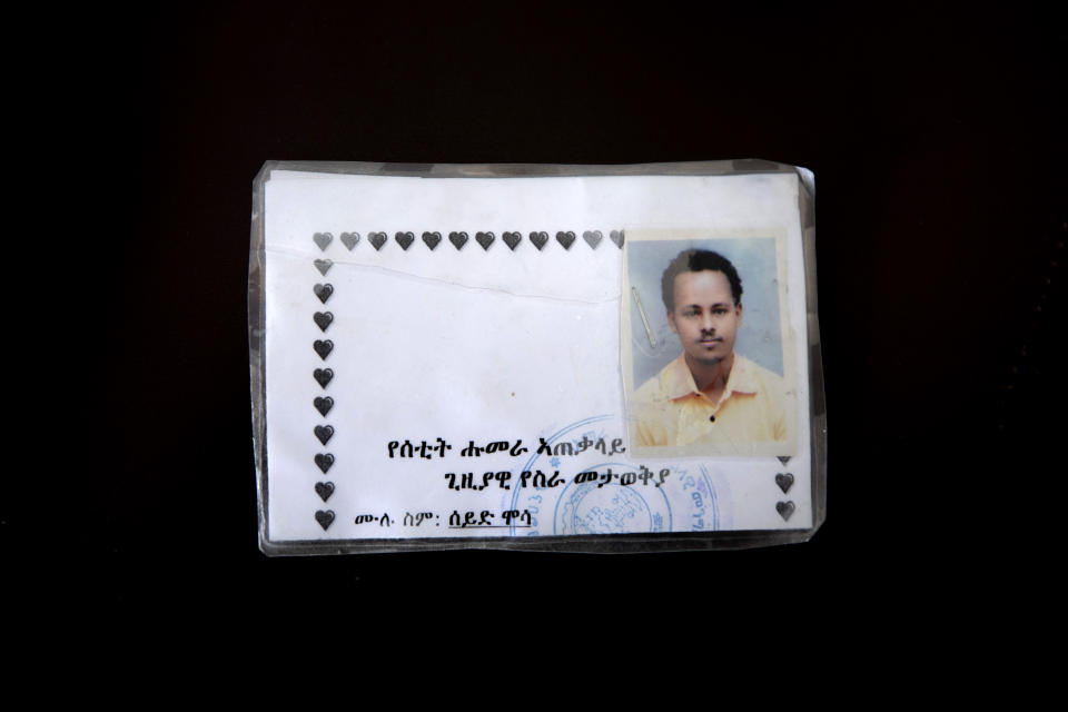 """This March 17, 2021 photo shows a new ID card issued by Amhara authorities to Seid Mussa Omar, a 29-year-old Tigrayan nurse from Humera, who fled to Hamdayet, eastern Sudan, near the border with Ethiopia. Amhara authorities took Omar's original ID card displaying his Tigrayan ethnicity and burned it, he said. On the new card examined by the AP, traces of Tigray had vanished. It was issued in January 2021 in a city located so far north in Ethiopia that it is within sight of neighboring Eritrea. Yet the card is stamped by authorities of the Amhara region to the south. The language on the card is Amharic, not the Tigrinya of Tigray. Translation from Amharic reads, """"Setit Humera General Temporary Work Place Identity — Full Name: Seid Mussa."""" (AP Photo/Nariman El-Mofty)"""