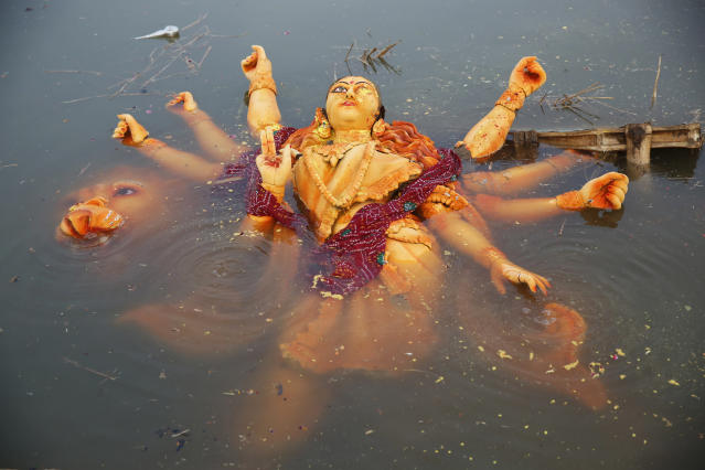 <p>An idol of the Hindu goddess Durga floats in a temporary pond near the River Ganges after its immersion in Allahabad, India, Saturday, Sept. 30, 2017. The immersion of idols marks the end of the festival that commemorates the slaying of a demon king by lion-riding, 10-armed goddess Durga, marking the triumph of good over evil. (Photo: Rajesh Kumar Singh/AP) </p>