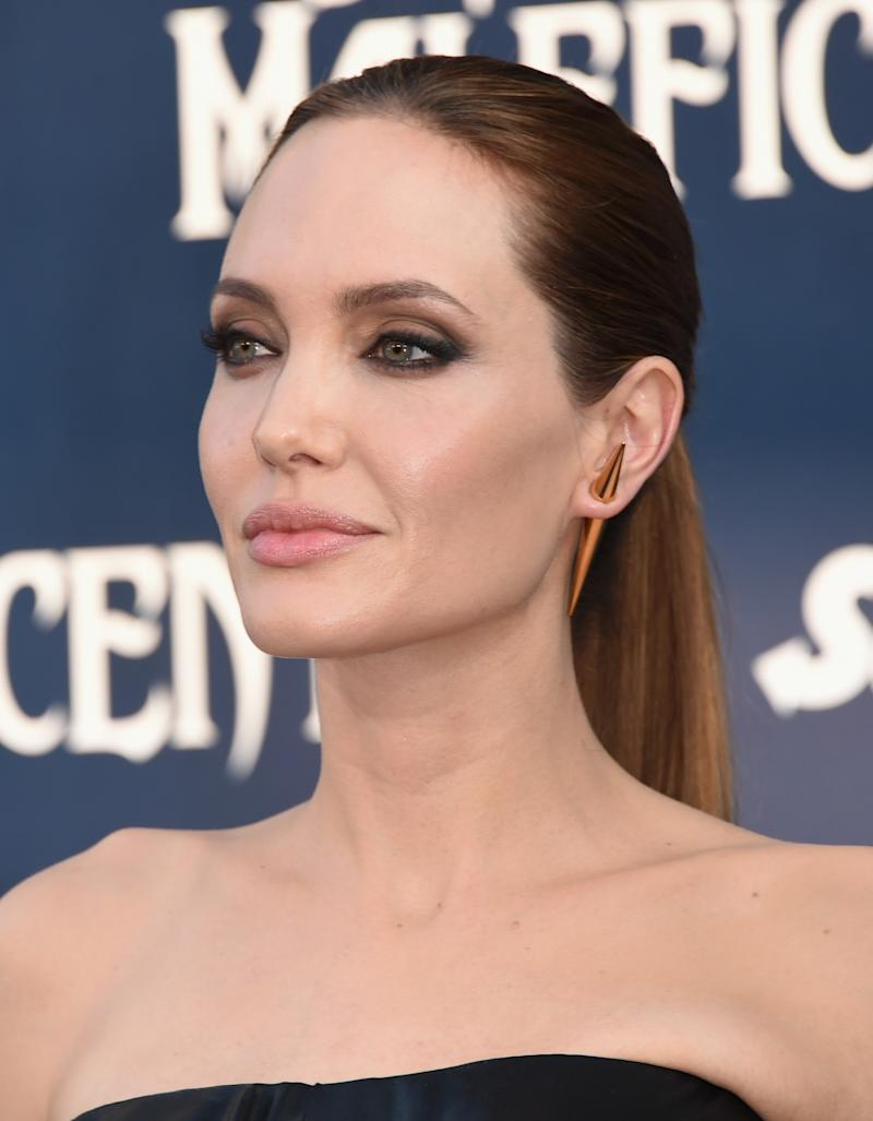 A sleek ponytail let her razor sharp cheekbones be the star. Maleficent in Hollywood, California, May 2014. Photo by Getty Images.