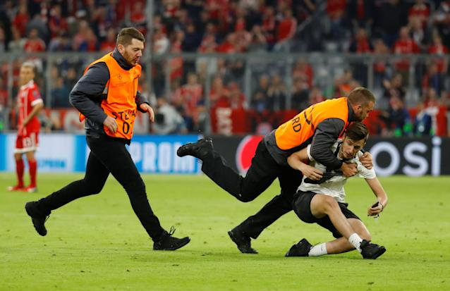 Soccer Football - Champions League Semi Final First Leg - Bayern Munich vs Real Madrid - Allianz Arena, Munich, Germany - April 25, 2018 A steward tackles a pitch invader after the match REUTERS/Kai Pfaffenbach