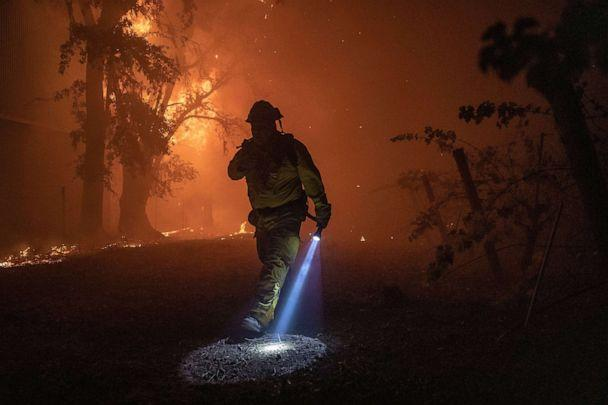 PHOTO: A firefighter walks past a building burning out of control, as the Kincade Fire continues to burn in Healdsburg, Calif., 27 Oct. 27, 2019. (Peter Dasilva/EPA via Shutterstock)