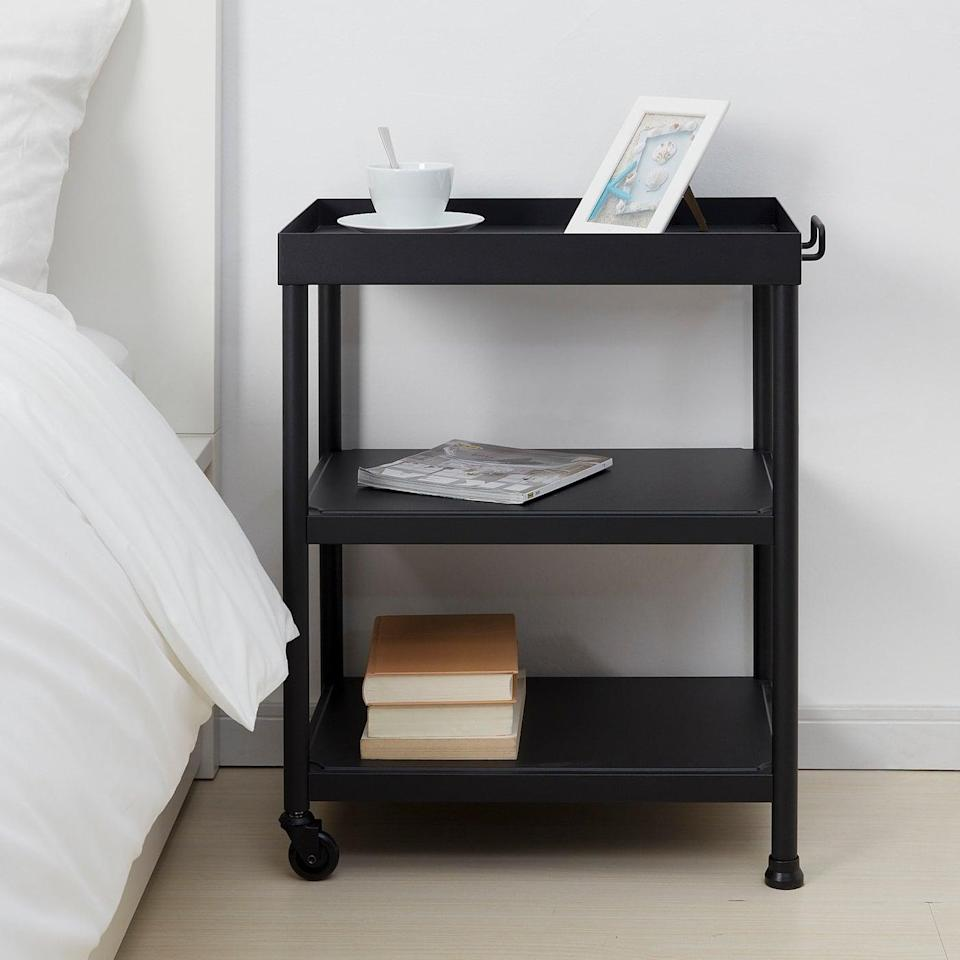 <p>This three-shelf <span>Kornsjö Side Table</span> ($50) has wheels on one side, so you can move it in and out of your bedroom depending on if you need it or not. Keep photos, books, and magazines on the roomy shelves.</p>
