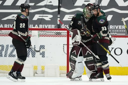 Arizona Coyotes defenseman Alex Goligoski, right, congratulates Coyotes goaltender Antti Raanta, center, after a win against the San Jose Sharks as teammate Johan Larsson, left, looks on after an NHL hockey game Saturday, Jan. 16, 2021, in Glendale, Ariz. The Coyotes defeated the Sharks 5-3. (AP Photo/Ross D. Franklin)