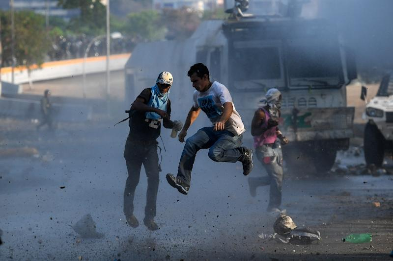 Anti-government protesters clash with security forces in Caracas during May Day celebrations (AFP Photo/Federico PARRA)