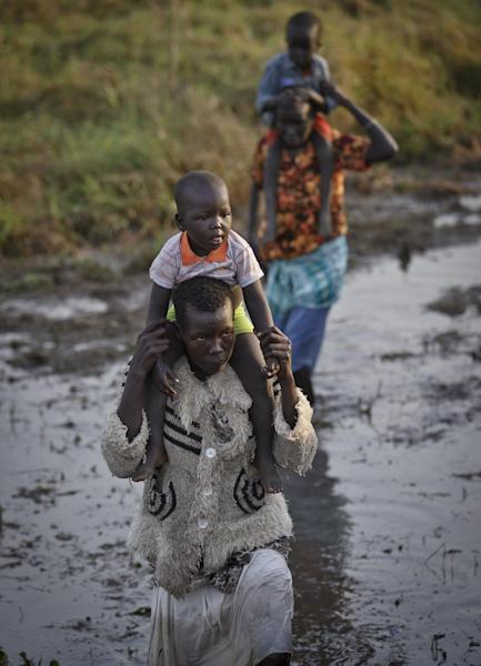 "Displaced people wade through mud as they get off a river barge from Bor, some of the thousands who fled the recent fighting between government and rebel forces in Bor by boat across the White Nile, in the town of Awerial, South Sudan Thursday, Jan. 2, 2014. The international Red Cross said Wednesday that the road from Bor to the nearby Awerial area ""is lined with thousands of people"" waiting for boats so they could cross the Nile River and that the gathering of displaced is ""is the largest single identified concentration of displaced people in the country so far"". (AP Photo/Ben Curtis)"