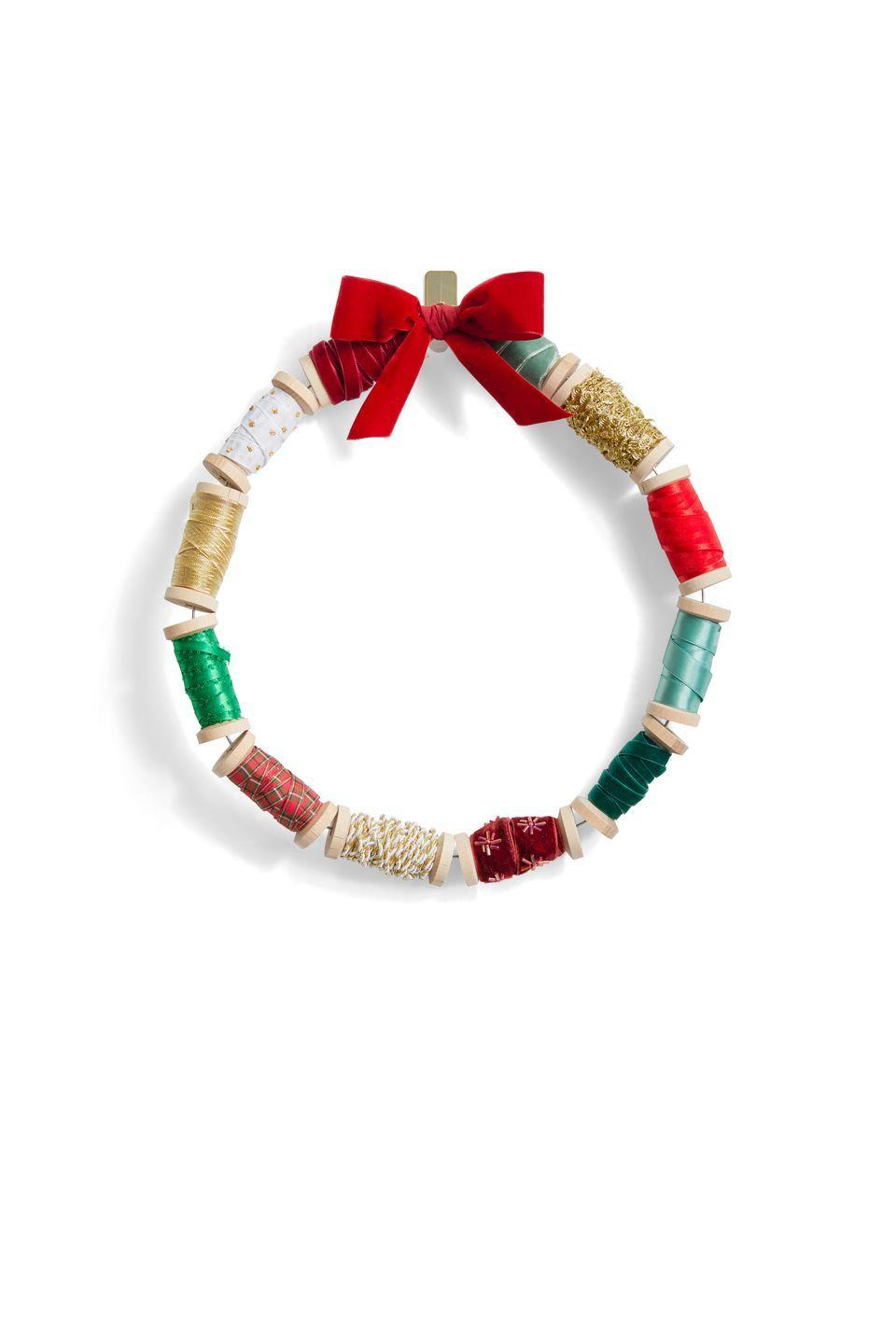 <p>Up for a simply DIY wreath? Grab your stash of empty spools and wrap them in ribbon. Hang your new wreath with wire, and you're ready to welcome holiday guests! </p>