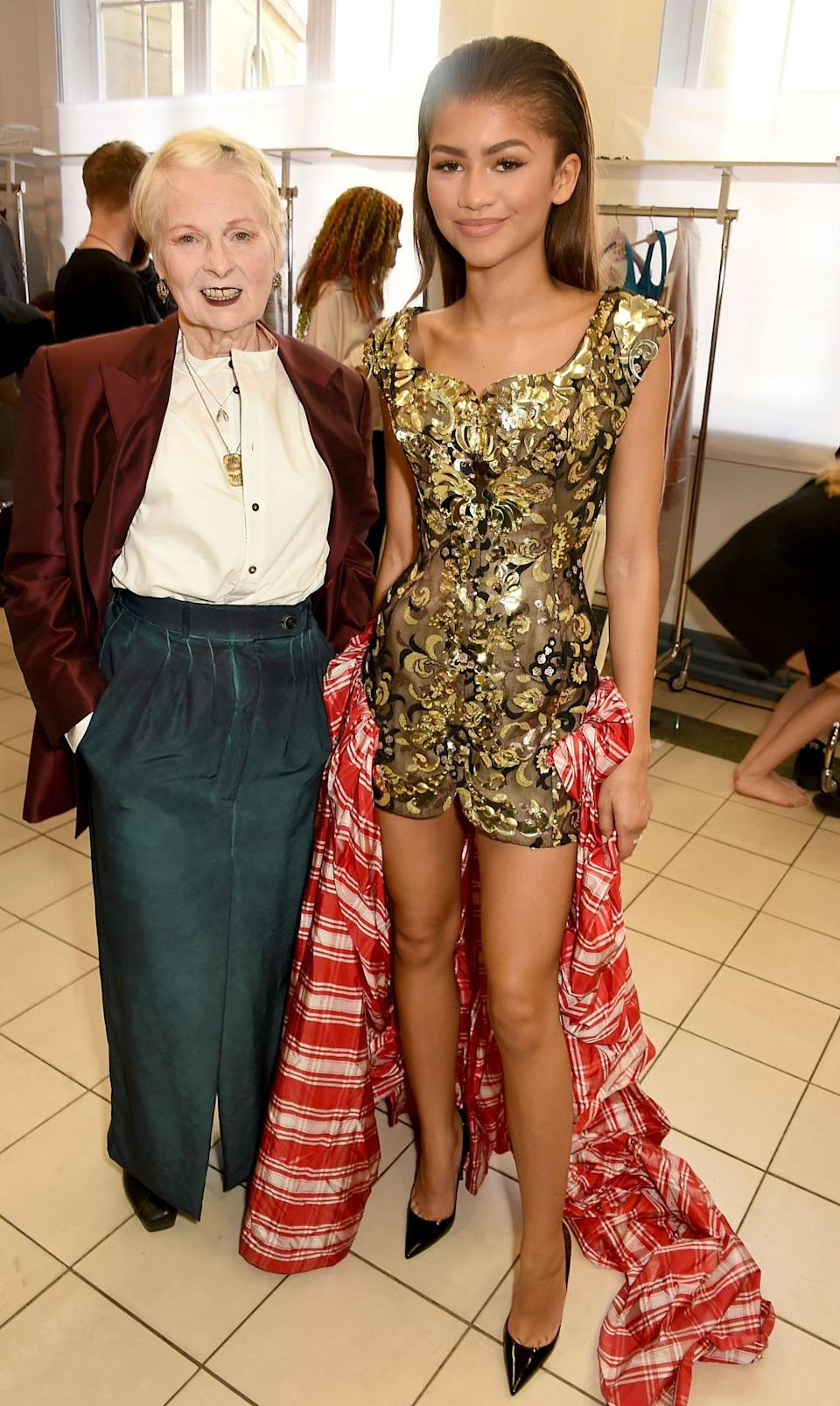 "<p>Backstage at Vivienne Westwood's Gold Label show in Paris (Red Label is in London), Zendaya wore the ""Fig"" dress, which is a mini dress and gown hybrid. What is that you ask? The fashion amalgam consists of a gold dress with a short hemline and a red and white tartan skirt attached at the hips with a long train. <br></p><p><i>Photo: Getty Images</i></p>"
