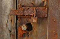 A lock corroded by sea water secures a storm damaged door on a property that is under threat of destruction from coastal erosion in Afidegnigban