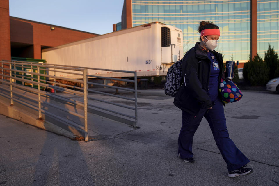 Nurse Jessica Franz walks past a mobile morgue at Olathe Medical Center after working the graveyard shift Thursday, Nov. 26, 2020, in Olathe, Kan. Franz lost her mother-in-law to COVID on Nov. 10 and was planning a scaled-back Thanksgiving with just her household. (AP Photo/Charlie Riedel)