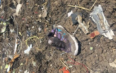 A shoe and other debris lie on the ground of the crash site