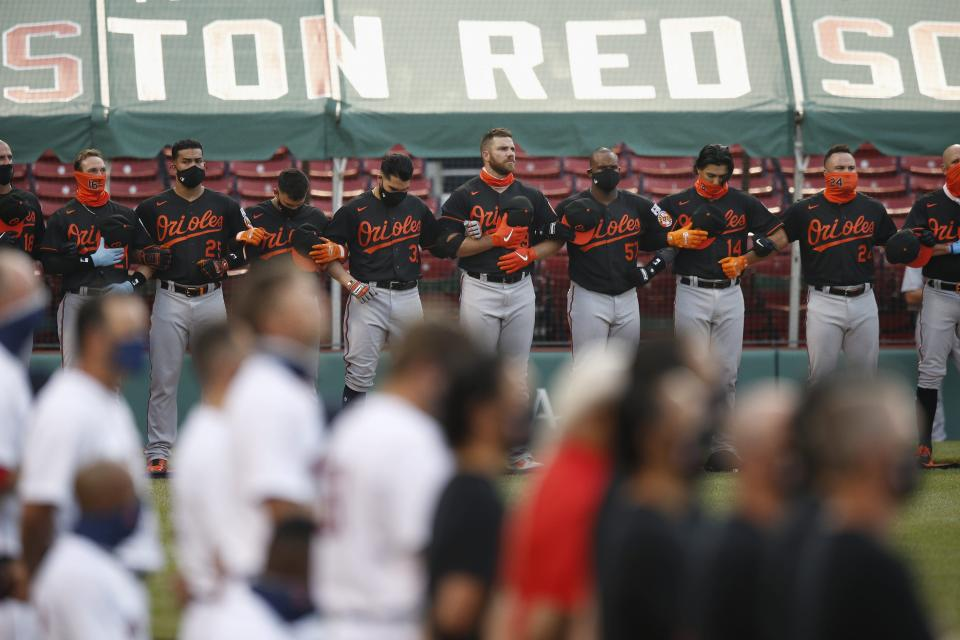The Boston Red Sox and the Baltimore Orioles line up on the base lines during the national anthem before an opening day baseball game at Fenway Park, Friday, July 24, 2020, in Boston. (AP Photo/Michael Dwyer)