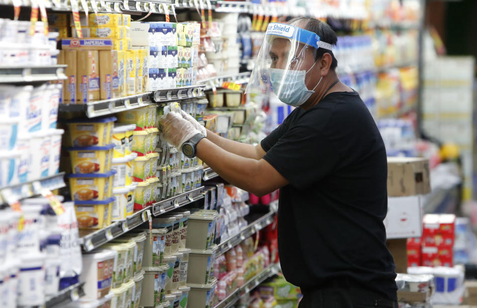 Amid concerns of the spread of COVID-19, a worker restocks products at a grocery store in Dallas, TX in April. (LM Otero/AP)