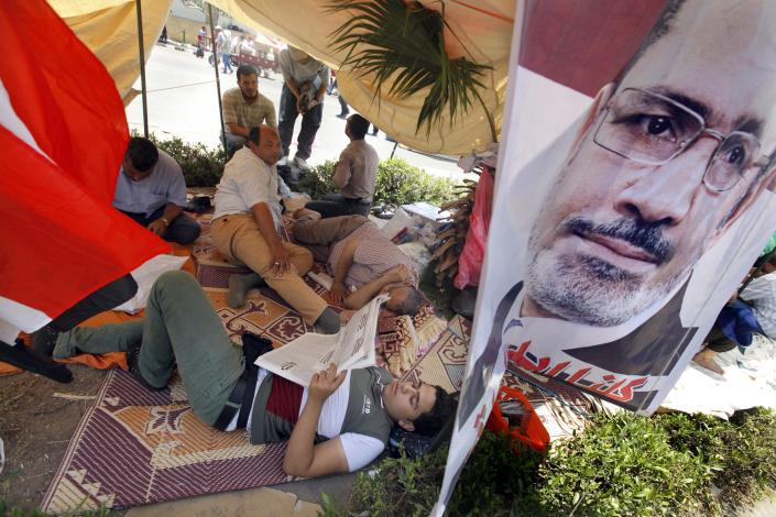Supporters of Egypt's Islamist President Mohammed Morsi rest at their tent with a poster of the president at a public square outside the Rabia el-Adawiya mosque near the presidential palace in Cairo, Saturday, June 29, 2013. Thousands of supporters and opponents of Egypt's embattled Islamist president held rival sit-ins in separate parts of Cairo Saturday on the eve of opposition-led mass protests aimed at forcing Mohammed Morsi from power. (AP Photo/Amr Nabil)