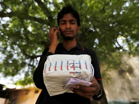 FILE PHOTO: A worker of Indian e-commerce company Snapdeal makes a call to a customer before delivering a packet in Ahmedabad