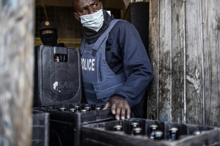 Confiscated: Crates of beer join other suspected stolen goods that police haul away from the hostel