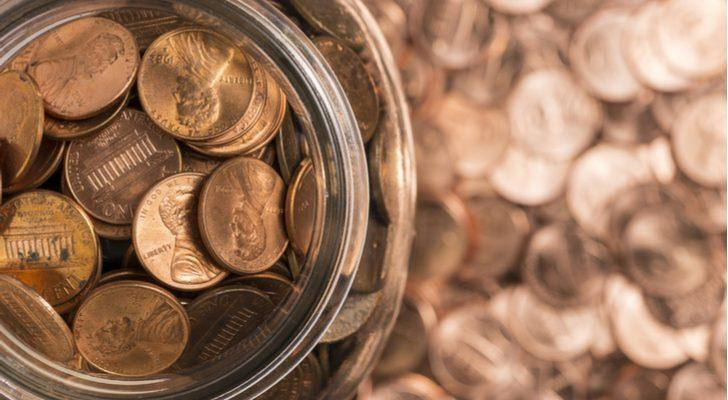 a jar filled with pennies on a table covered in pennies to represent penny stocks