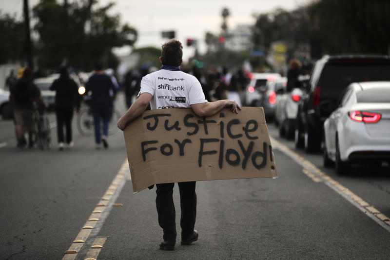 A demonstrator walks with a sign during a protest Monday, June 1, 2020, in Anaheim, Calif., over the death of George Floyd on May 25 in Minneapolis. (AP Photo/Jae C. Hong)