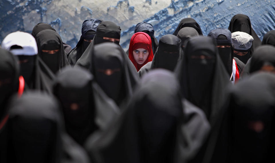 <p>A female anti-government protestor, center, wearing a red scarf, looks on while praying with other women during a demonstration demanding the resignation of Yemeni President Ali Abdullah Saleh, in Sanaa,Yemen, April 6, 2011. (Photo: Muhammed Muheisen/AP) </p>