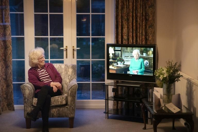 Val Cloke sits in her living room in the village of Hartley Wintney watching Queen Elizabeth II deliver a special address to the UK and Commonwealth about the coronavirus outbreak