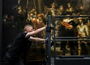 """An employee moves scaffolding from in front of Rembrandt's """"The Night Watch"""""""