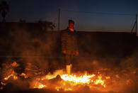 A man warms himself by a fire in dumped garbage during a sudden cold front near Johannesburg, Saturday, Aug. 28, 2021. (AP Photo/Ali Greeff)