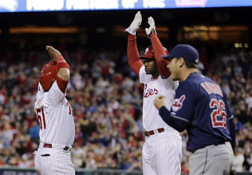 Philadelphia Phillies' Carlos Ruiz, left, and Domonic Brown celebrate after scoring on a double by John Mayberry Jr. as Cleveland Indians starting pitcher Scott Kazmir, right, walks to the mound in the fourth inning of a baseball game, Tuesday, May 14, 2013, in Philadelphia. (AP Photo/Matt Slocum)