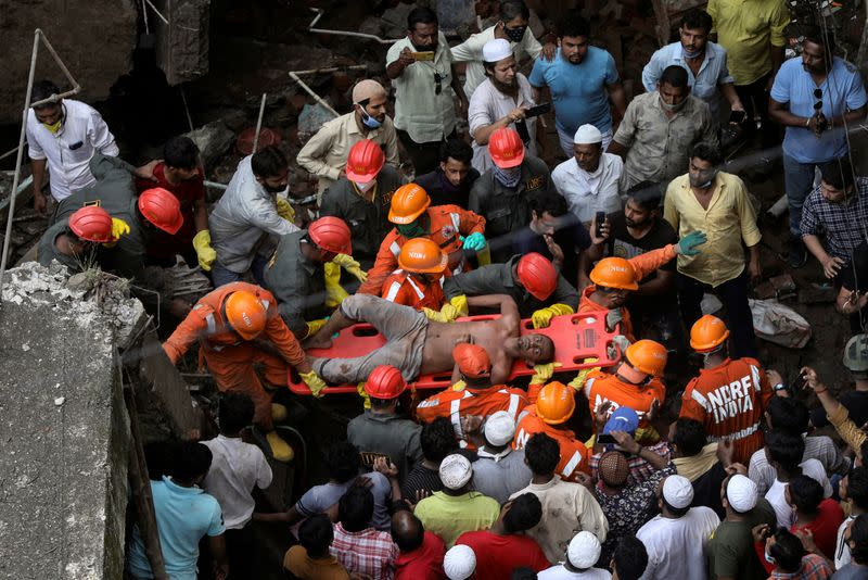 National Disaster Response Force (NDRF) officials rescue a man from the debris after a three-storey residential building collapsed in Bhiwandi on the outskirts of Mumbai, India