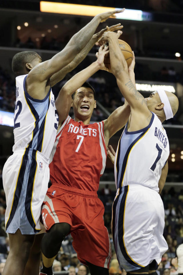 Houston Rockets guard Jeremy Lin, center, tries to shoot between Memphis Grizzlies' Ed Davis, left, and Jerryd Bayless, right, during the first half of an NBA preseason basketball game in Memphis, Tenn., Friday, Oct. 25, 2013. (AP Photo/Danny Johnston)