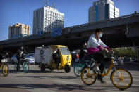 Commuters wearing face masks to protect against the coronavirus ride bicycles across an intersection in Beijing, Thursday, Oct. 22, 2020. The number of confirmed COVID-19 cases across the planet has surpassed 40 million, but experts say that is only the tip of the iceberg when it comes to the true impact of the pandemic that has upended life and work around the world. (AP Photo/Mark Schiefelbein)