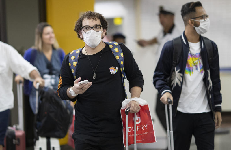 Passengers wear masks as a precaution against the spread of the new coronavirus COVID-19 after their plane landed at the Sao Paulo International Airport in Sao Paulo, Brazil, Thursday, Feb. 27, 2020. (AP Photo/Andre Penner)