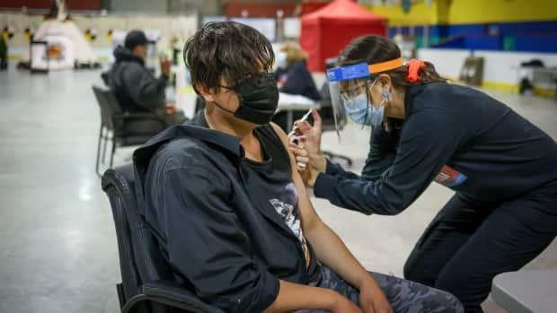 Joziah Calf Robe, 17, receives a COVID-19 vaccine at the Siksika Nation rural COVID-19 immunization clinic at the Deerfoot Sportsplex last month. As of Sunday, more than 5 million doses of COVID-19 vaccines have been administered in Alberta.  (AHS - image credit)