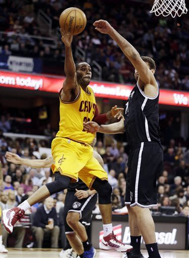 Cleveland Cavaliers' Wayne Ellington, left, passes in front of Brooklyn Nets' Brook Lopez (11) in the second quarter of an NBA basketball game, Wednesday, April 3, 2013, in Cleveland. (AP Photo/Tony Dejak)