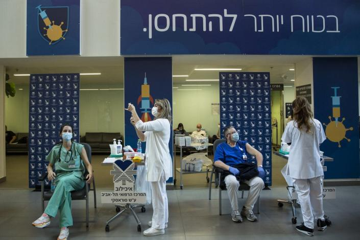 Nurses prepare to give medical workers vaccines.
