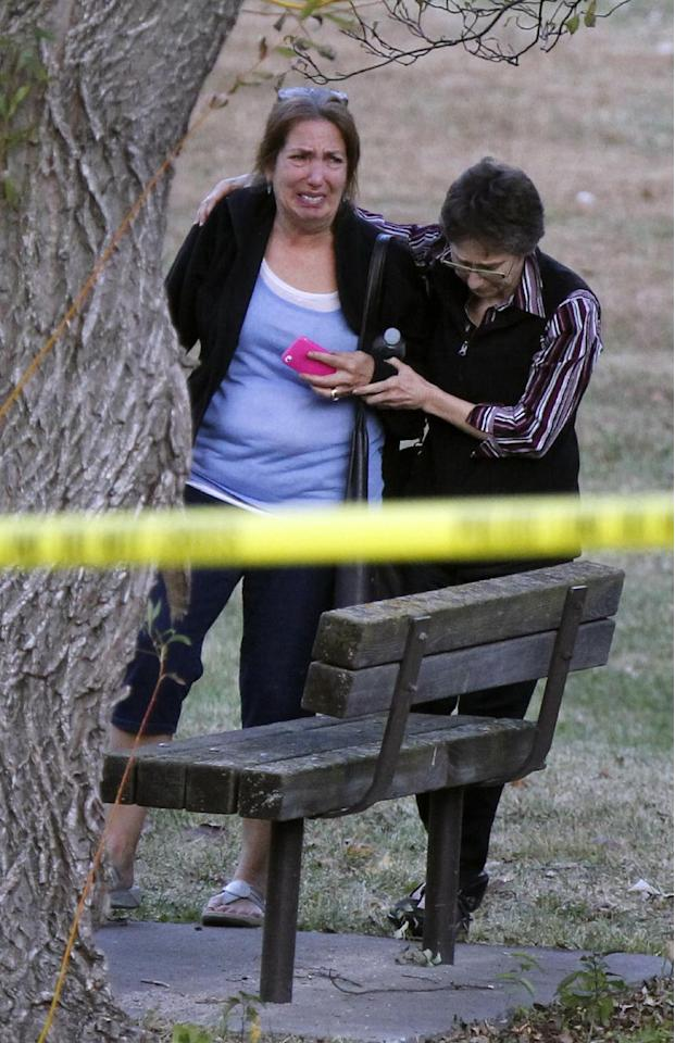 An unidentified woman is consoled at the scene of a shooting that left at least two dead and four others wounded at Accent Signage Systems in Minneapolis, Thursday, Sept. 27, 2012. (AP Photo/The Star Tribune, Richard Tsong-Taatarii) MANDATORY CREDIT; ST. PAUL PIONEER PRESS OUT; MAGS OUT; TWIN CITIES TV OUT
