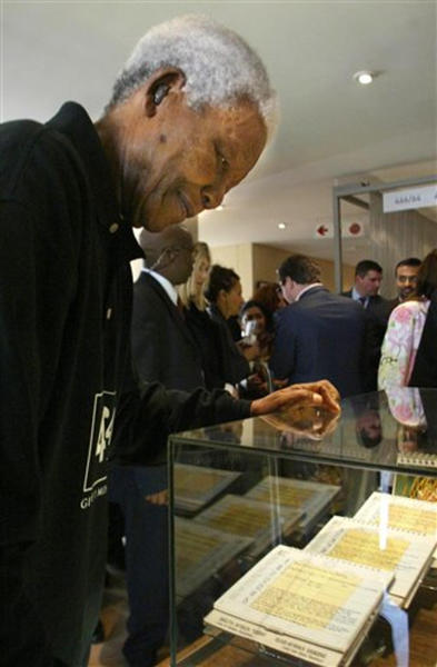 FILE - In this Tuesday, Sept. 21, 2004, file photo, Former South African President Nelson Mandela, looks at some of the personal letter he wrote in prison, at the launch of the Nelson Mandela Center for Memory and Commemoration in Johannesburg, South Africa. Most of Nelson Mandela's handwriting is neat, but it harbors a few mysteries. Archivists sometimes struggle to decipher words in the vast body of documents that Mandela penned, and he often jotted an acronym that nobody, not even the former South African president in later years, has been able to explain. (AP Photo/Themba Hadebe, FILE)
