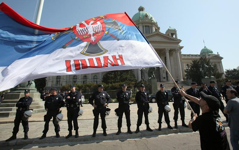 A protester holds an Serbian flag during a rally in front of Serbia's parliament building in Belgrade, Serbia, Friday, April 26, 2013. Serbian lawmakers are debating an EU-brokered deal on normalization of ties with breakaway Kosovo which was signed by the government and sets the former war foes on the path of reconciliation and EU integration. (AP Photo/Darko Vojinovic)