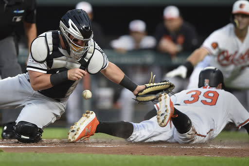 Chicago White Sox catcher James McCann loses the ball as Baltimore Orioles' Renato Nunez slides safely across the plate on a RBI single by Rio Ruiz in the first inning of a baseball game, Wednesday, April 24, 2019, in Baltimore. (AP Photo/Gail Burton)