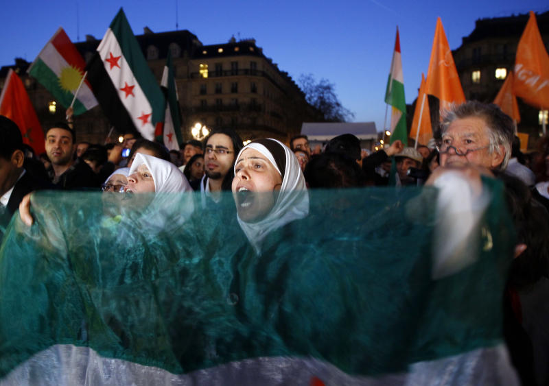 Protesters holding Syria flags shout slogans during a rally to support the Syrian people on the first anniversary of the Syrian uprising, in front of Paris City hall in Paris, Thursday March 15, 2012. (AP Photo/Francois Mori)