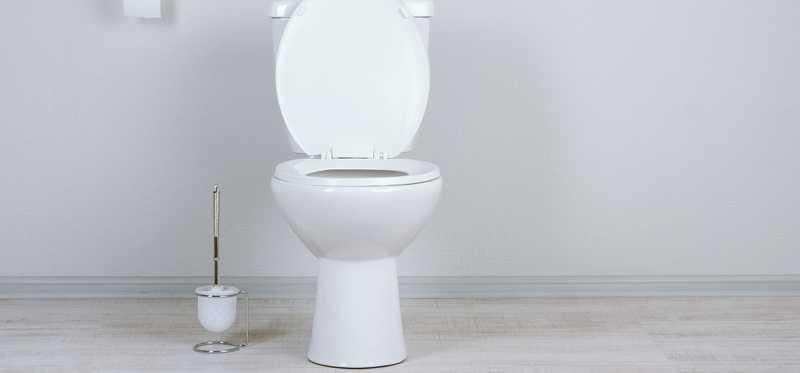 A white toilet in a white bathroom.