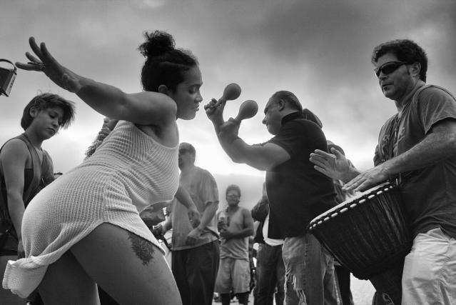 <p>A young woman dances to the entrancing rhythms at the Venice Beach Drum Circle, as the sun sets over the ocean on a warm summer evening. (© Dotan Saguy) </p>
