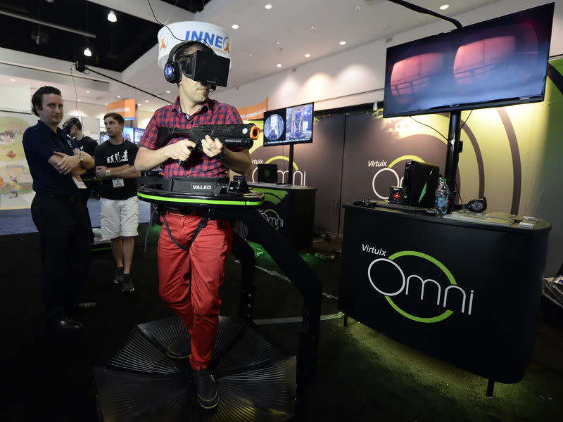 4a36b5614f5 An attendee tries out the Virtuix Oculus Rift and Omni Treadmill game at  the 2014 Electronic